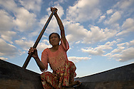 A woman paddles a dugout canoe on the Inle Lake, Myanmar.