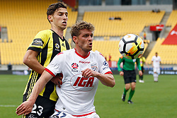 Adelaide United's Nikola Mileusnic, right, keeps his eye on the ball as he keeps Phoenix's Matthew Ridenton at bay iin the A-League football match at Westpac Stadium, Wellington, New Zealand, Sunday, October 08, 2017. Credit:SNPA / Dean Pemberton **NO ARCHIVING**