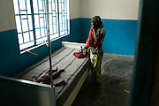 Marie Tabeh wipes a tear as she stands next to the bed where her two-year-old son Blackie lies suffering from severe dehydration at the Yoni PHU in the village of Yoni, on Sherbro Island, Sierra Leone on Thursday April 22, 2010.