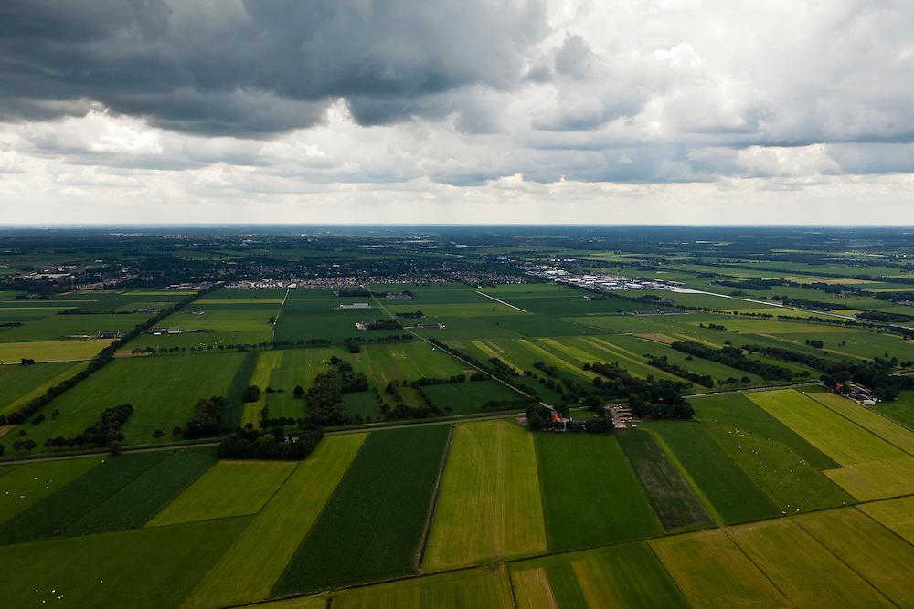 Nederland, Overijssel, Gemeente Twenterand, 30-06-2011; Landschap ten noorden Vriezenveen (aan de horizon). Voorbeeld van vroege ruilverkaveling (jaren '50)..De oorspronkelijk (zeer) smalle en lange kavels, ontstaan door het ontginnen van veen, zijn samengevoegd tot grotere blokken en veelal is het kavelpatroon 90 graden gedraaid. De globale oorspronkelijke - onderliggende - structuur is deels nog herkenbaar..Naast de gedraaide verkalveling zijn verder kenmerkend de 'boerderijstraten', linten van boerderijen omgeven door singels van bomen (diagonaal in het midden). verder de 'boerderijstraten', linten van boerderijen omgeven door singels van bomen..Landscape north of Vriezenveen, an early example of land consolidation (50s)..The original (very) long and narrow lots, created by the extraction of peat, are merged into larger blocks and in most cases the plot pattern has been rotated 90 degrees  The original - underlying - structure is still partly visible..Further characteristic features are the 'farm roads' with farmhouses surrounded by belts of trees..luchtfoto (toeslag), aerial photo (additional fee required).copyright foto/photo Siebe Swart