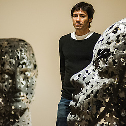 London, UK - 2 September 2014: Artist Xavier Mascaró poses next to 'Head of Eleonora' (left) and 'Head of Alexandra' (Right)  reminiscent of the profiles on ancient coins. Xavier Mascaró's first UK solo exhibition will run from 3 September until 5 October at Saatchi Gallery.