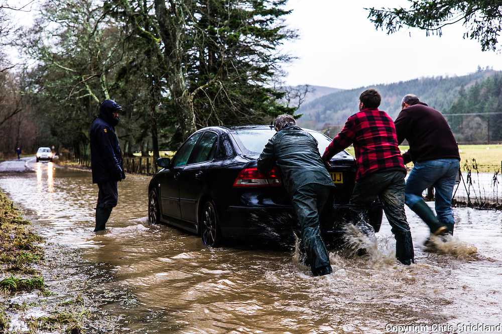 Yarrow, Selkirk, Scottish Borders, UK. 30th December 2015. A broken down car due to water in the engine is pushed through a flood as Storm Frank moves across the South of Scotland.