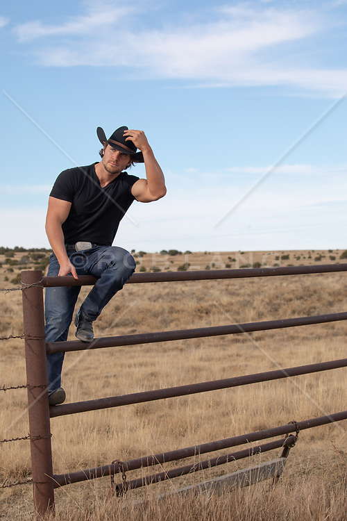 cowboy sitting on a fence in rural America