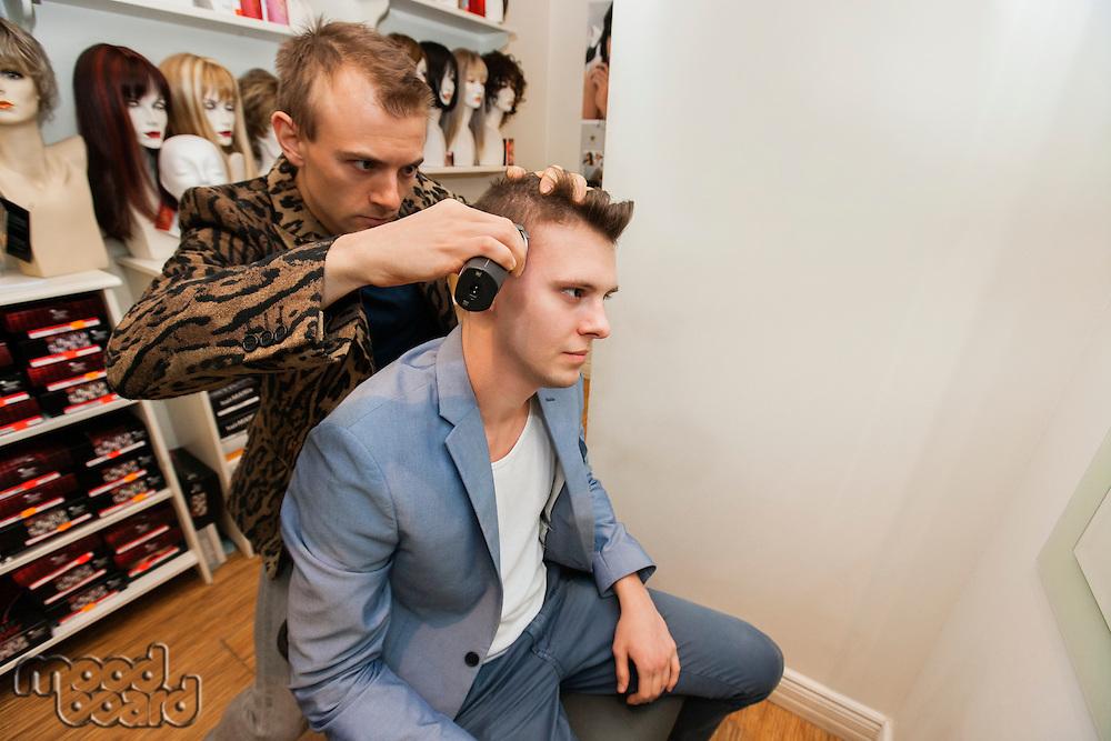 Barber shaving male customer's hair in shop