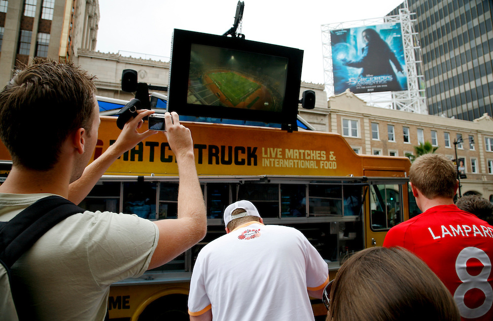 As England and the United States compete in the World Cup fans gather to watch televised coverage at the ESPN Match Truck parked on Hollywood Boulevard in Hollywood California, USA, 12 June 2010.