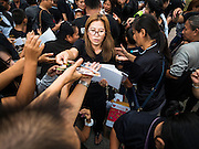 17 OCTOBER 2016 - BANGKOK, THAILAND: A woman hands out portraits of Bhumibol Adulyadej, the late King of Thailand, at Sanam Luang in central Bangkok. Thai King Bhumibol Adulyadej died Oct. 13, 2016. He was 88. His death comes after a period of failing health. Bhumibol Adulyadej, was born in Cambridge, MA, on 5 December 1927. He was the ninth monarch of Thailand from the Chakri Dynasty and is also known as Rama IX. He became King on June 9, 1946 and served as King of Thailand for 70 years, 126 days. He was, at the time of his death, the world's longest-serving head of state and the longest-reigning monarch in Thai history.        PHOTO BY JACK KURTZ