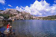 Woman purifying drinking water on the shore of Boothe Lake, Sierra Nevada Mountains, Yosemite National Park, California