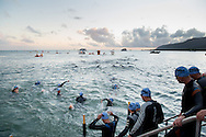 70.3 Competitors make their way into the water for the swim start. Ironman Cairns and Ironman Cairns 70.3 Race. 2013 Ironman Cairns Triathlon Festival. Cairns, Queensland, Australia. 09/06/2013. Photo By Lucas Wroe