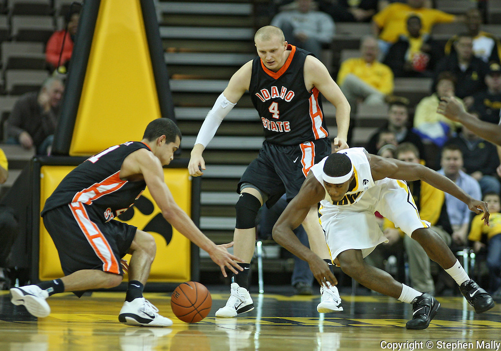 December 04 2010: Idaho State Bengals forward/center Abner Moreira (21) and Iowa Hawkeyes forward Melsahn Basabe (1) battle for a lose ball as Idaho State Bengals center Kamil Gawrzydek (4) looks on during the first half of their NCAA basketball game at Carver-Hawkeye Arena in Iowa City, Iowa on December 4, 2010. Iowa won 70-53.