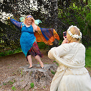 Old Westbury, New York, U.S. 22nd June 2013. CRYSTAL MALARSKY takes a cell phone photo of her friend EMILY CAROLINE, both from Astoria and wearing elaborate fairy costumes, at the Midsummer Night event at Old Westbury Gardens, on the grounds of the historic Long Island Gold Coast estate.