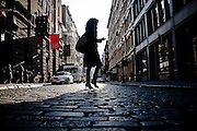 Back-lightened silhouette of a girl walking on the pavement of Greene Street in SoHo, Manhattan, New York, 2009.