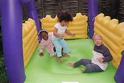 Multiracial group of children playing together on bouncy castle,