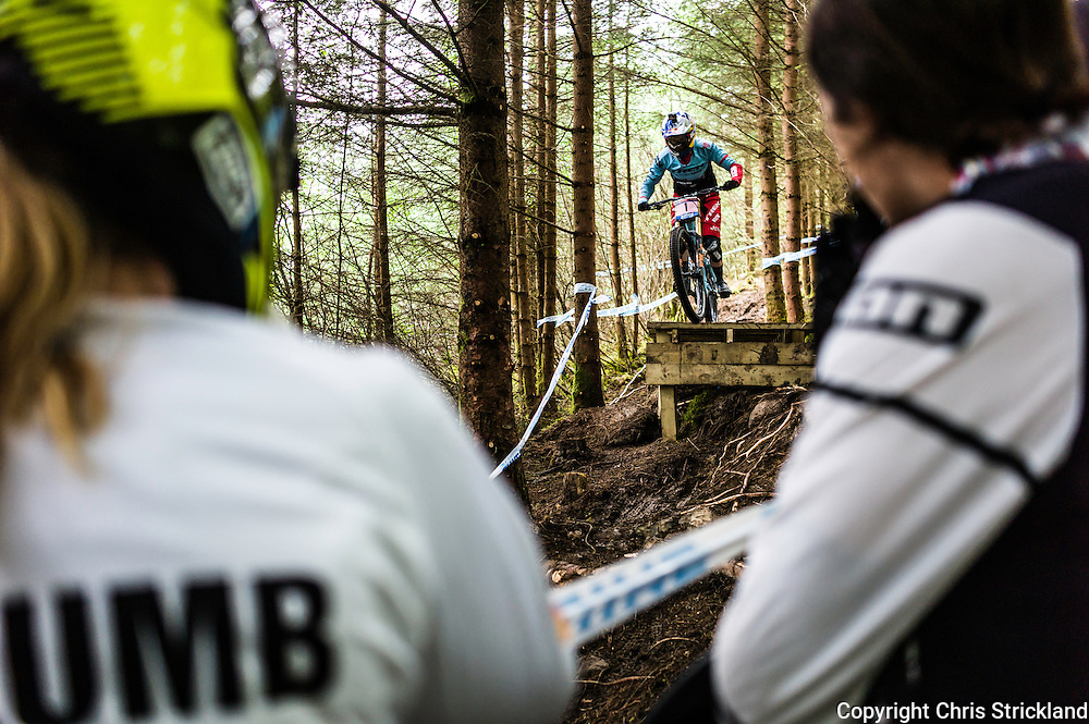 Nevis Range, Fort William, Scotland, UK. 4th June 2016. World champion Rachel Atherton of Great Britain tackles the wooded section of the course watched on by fellow competitors. The worlds leading mountain bikers descend on Fort William for the UCI World Cup on Nevis Range.
