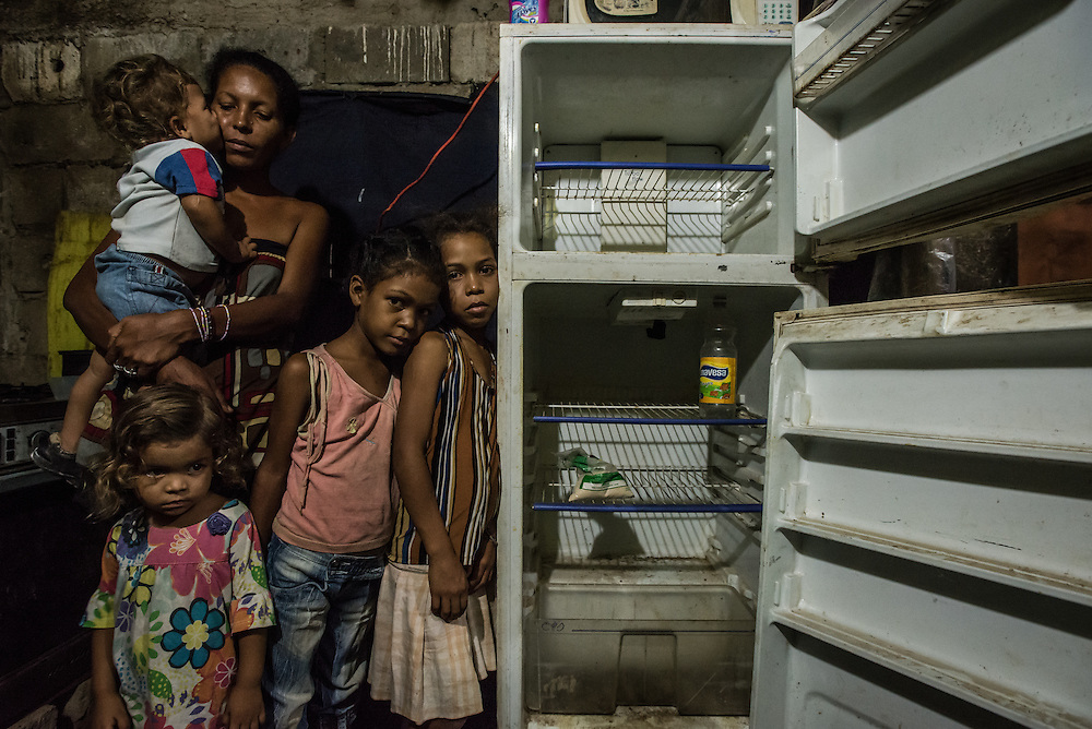"CUMANÁ, VENEZUELA - JUNE 16, 2016: Leidy Cordova, a 37-year-old mother, poses for a portrait with four of her five children: Abran, 1, Deliannys, 3, Eliannys, 6, and Milianny, 8-years old. The entire family went the entire day without eating.  They hadn't eaten since lunchtime the day before...a soup made by boiling chicken skin and fat,  that is sold for a much cheaper price than  chicken at the butcher.  Inside their home, a cinderblock structure on the edge of the highway, a broken refrigerator was empty except for half a bag of corn flour and a bottle of vinegar. That was the only food they had in their entire house, and Ms. Cordova was worried about if she would be able to find a way to feed her children tomorrow.  ""My kids tell me they're hungry,"" said Ms. Cordova as her family looked on. ""And I all can say to them is to grin and bear it."" PHOTO: Meridith Kohut"