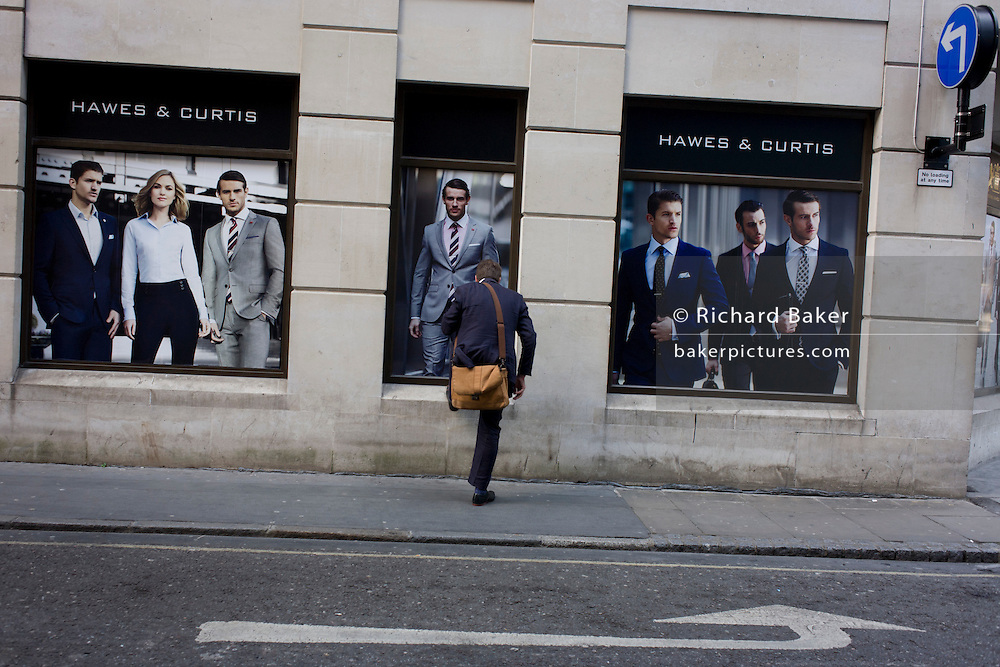 A businessman puts a foot up on the sill of a menswear shop called Hawkes & Curtis in the City of London. From behind, it looks as if he has only on leg, such is the moment and the perspective. The image is also slightly off the level and is a visual pun on the arrows in the road and on the building's wall that suggest the computer command to rotate the picture left.