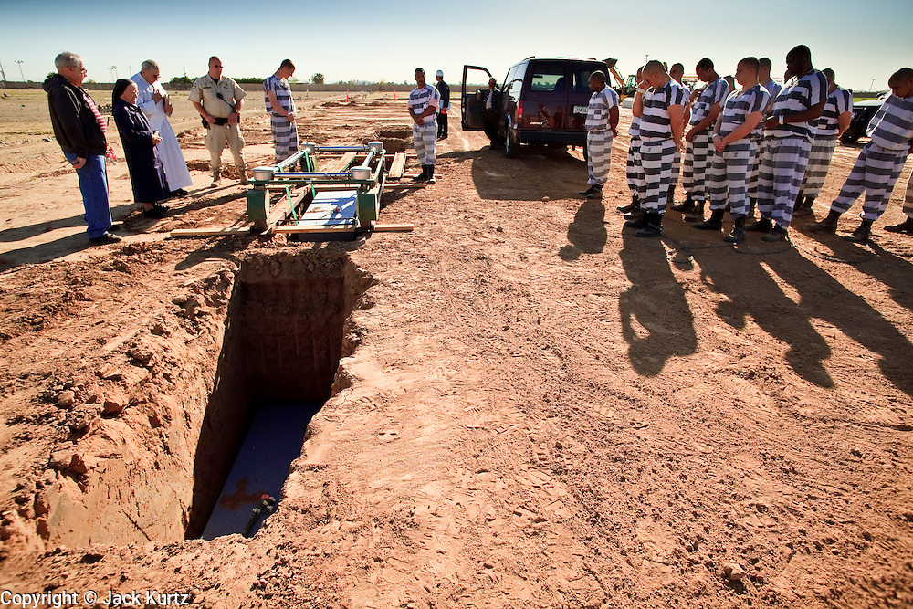"""18 MARCH 2010 - SURPRISE, AZ:  Members of the Maricopa County Sheriff's Dept """"Chain Gang"""" work to bury people in White Tanks Cemetery on Camelback Rd. in an unincorporated part of the county near Surprise. The county spent about $2.5 million to inter indigent people in what is Maricopa County's """"potters field."""" About 3,000 people, children and adults, are buried in the dusty field west of Phoenix.  PHOTO BY JACK KURTZ"""