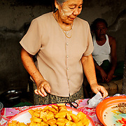 Elderly woman cooking tofu at rural market
