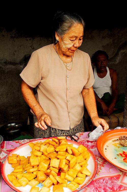 Elderly woman cooking tofu at rural market