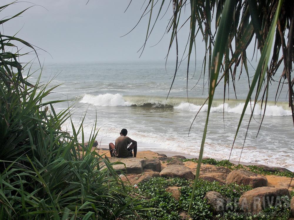 A young man sits on a beach close to Hikkaduwa, Sri Lanka, on February 26, 2011.