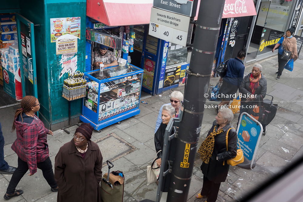Shoppers wait for the next bus service at a bus stop on the Walworth Road in Southwark on 11th June 2019, in London, England.