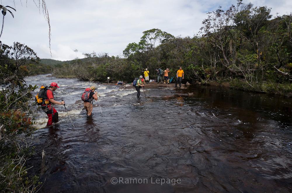 """AUYANTEPUY, VENEZUELA. Excursionistas cursando el río Churum  durante travesía del tepuy. El Auyantepuy es el mayor de los tepuis del Parque Nacional Canaima. En sus 700 kms2 alberga el salto angel o conocido por lengua indígena Pemon como """"Kerepacupai Vena; es la caída de agua más grande del mundo con sus 979 metros de altura. (Ramon lepage /Orinoquiaphoto/LatinContent/Getty Images)"""