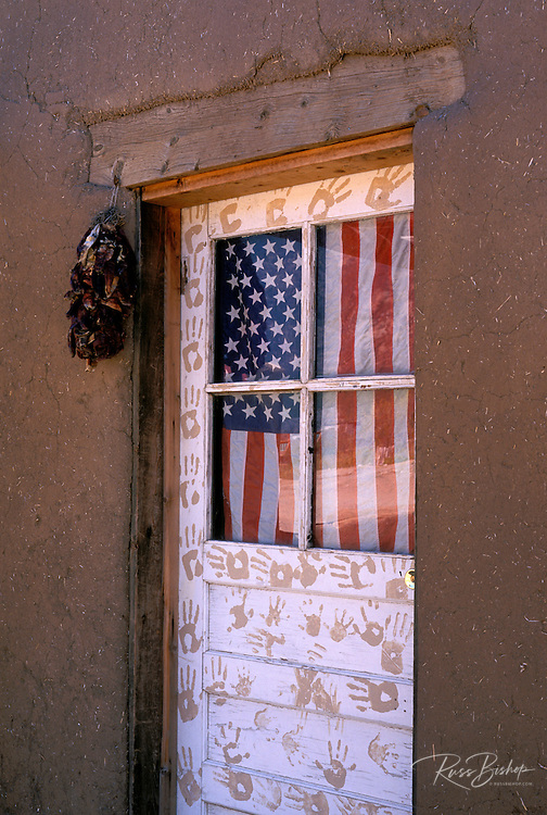 American flag in the door of an adobe house (World Heritage Site), Taos Pueblo , New Mexico