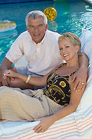 Senior couple sitting on deck chair by swimming pool, portrait