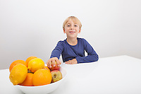 Portrait of boy with fruit bowl at table