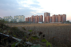 China, Beijing, Ping Fang Xiang, 2008. The new red buildings of Ding Fu Jia Yuan are part of a massive building expansion within the village of Ping Fang Xiang. All of the empty fields shown here in October, 2007 were under construction by March, 2008..