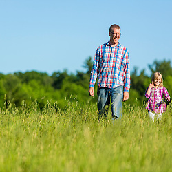A man and his young daughter walk in a field in Epping, New Hampshire.