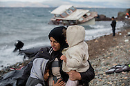 A woman holds her two children on a beach near Eftalou on the island of Lesvos, Greece after arriving from the North Coast of Turkey on a rubber raft on November 24, 2015.