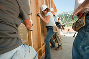 PRICE CHAMBERS / NEWS&amp;GUIDE<br /> Lisa Wolfgang, a Habitat for Humanity home recipient, works with contractors to raise a wall, framing her family's new garage last September.