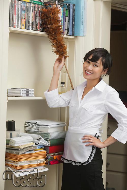 Portrait of female housekeeper dusting shelf