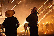 Two Mexican cowboys watch dozens of sky rockets explode from relative safety during the chaos of the Alborada festival September 29, 2018 in San Miguel de Allende, Mexico. The unusual festival celebrates the cities patron saint with a two hour-long firework battle at 4am representing the struggle between Saint Michael and Lucifer.