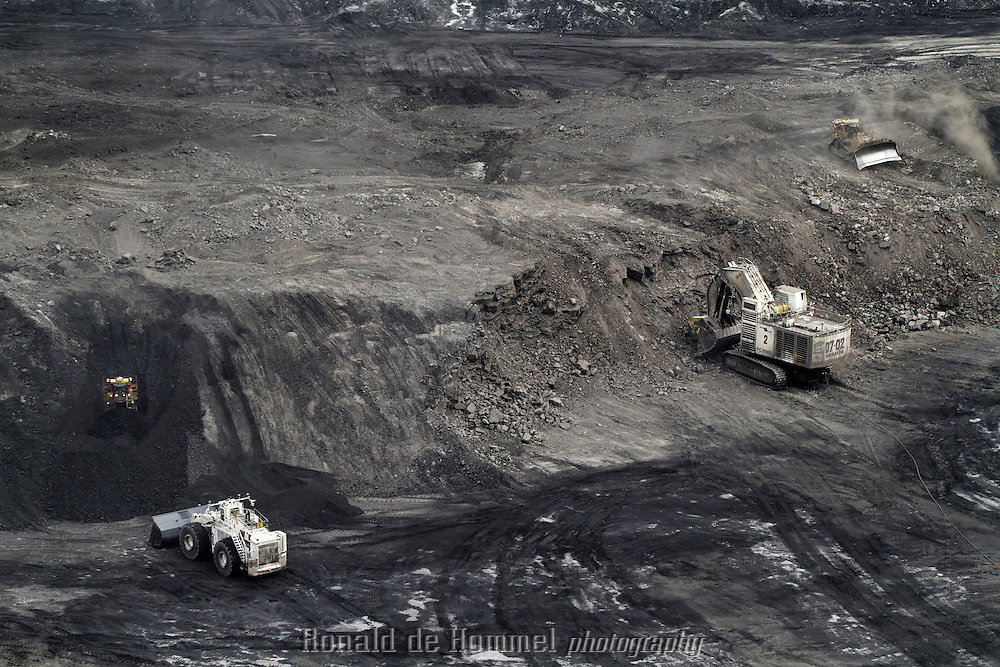 Gigantic coal trucks are dwarfed by the sheer size of the Cerrejon coal mine in 'La Guajira' state in east Colombia. this is one of the largest open pit mines in the world.  <br /> <br /> A large part of this high quality coal is exported to Europe where many organizations protest against Colombian coal (not only from Cerrejon) because of supposed labor abuses and environmental pollution. Cerrejon does not have any labor disputes, though many of their subcontractors have.<br /> Another criticism is that Cerrejon is planning to move the course of a river to expand the mined area. Local indigenous tribes vehemently oppose to this proposed destruction of their main water source in a semi desert landscape.