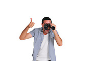 Excited Young man in his early 20s looking through a binoculars gives the thumb up sign