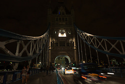 © Licensed to London News Pictures. 05/07/2014. London, UK. Tower Bridge in London is seen with lights switched off as traffic and people pass. Landmarks across London and the UK are turning their lights off from 10pm to 11pm tonight to mark the First World War centenary. Photo credit : Vickie Flores/LNP
