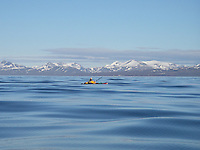 A kayak is almost hidden by the rolling waves on the Isfjord at Spitzbergen