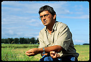 Foreman Rubimar dos Santos Leitzke kneels in rice field talking about Granja Bretanhas farm; RS. Brazil