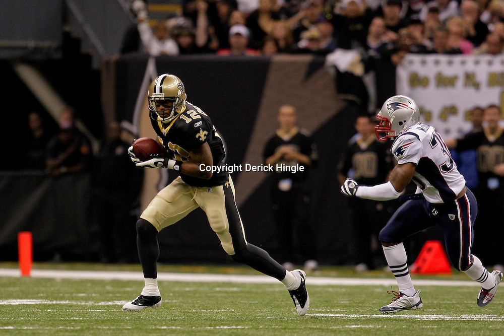 2009 November 30: New Orleans Saints wide receiver Marques Colston (12) runs from New England Patriots safety Brandon McGowan (30) during a 38-17 win by the New Orleans Saints over the New England Patriots at the Louisiana Superdome in New Orleans, Louisiana.