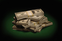 Bundles of US $100 bills on green felt under a spotlight