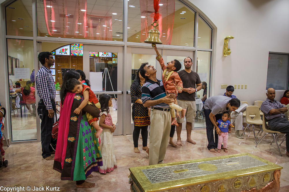 10 AUGUST 2012 - PHOENIX, AZ:   A family rings a bell as they enter the temple during the celebration of Janmashtami at Ekta Mandir, a Hindu temple in central Phoenix. Janmashtami is the Hindu holy day that celebrates the birth of Lord Krishna. Hindu communities around the world celebrate the holy day. In Arizona, most of the Hindu temples in the Phoenix area have special celebrations of the day.   PHOTO BY JACK KURTZ