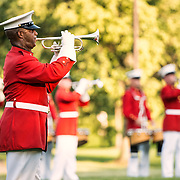 A bugler with the United States Marine Drum and Bugle Corps, known as the Commandant's Own, performing at the Sunset Parade at the Iwo Jima Memorial in Arlington, Virginia, next to Arlington National Cemetery.
