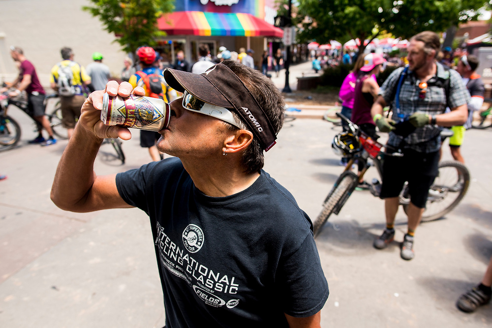 A racer takes a deep swig of beer after finishing his ride Saturday.