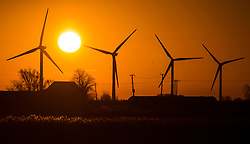 © Licensed to London News Pictures. 19/01/2020. Pondersbridge UK. The sun rises this morning over a house & surrounding wind turbines in the village of Pondersbridge in the Cambridgeshire Fens. Photo credit: Andrew McCaren/LNP