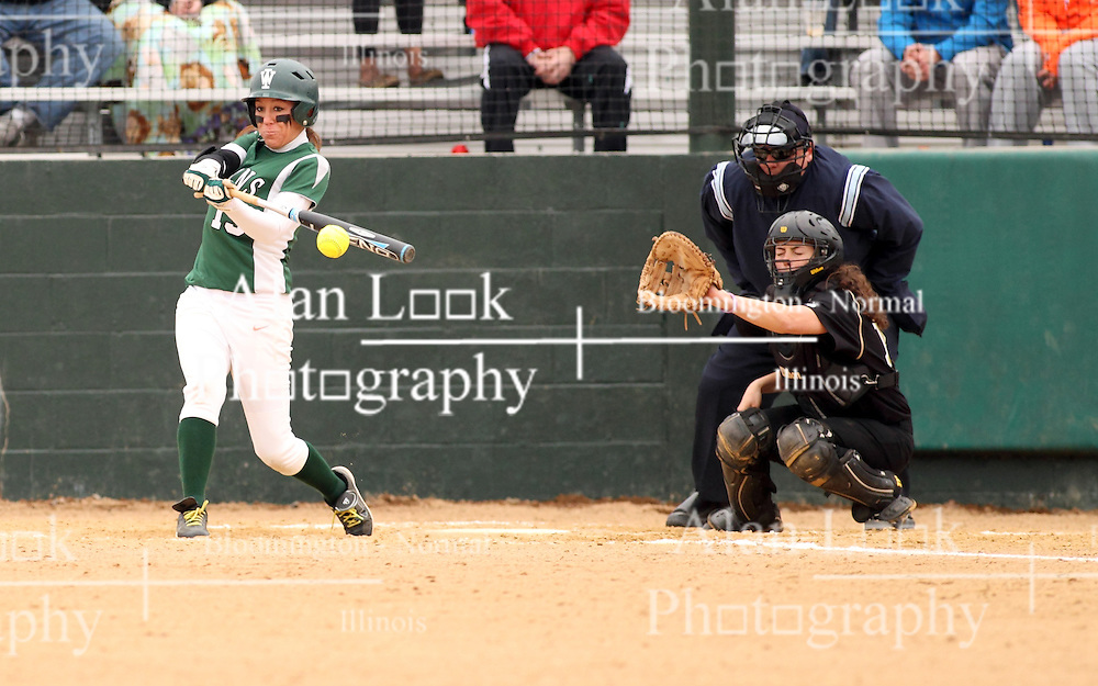 30 March 2013:  Allie Riordan batting during an NCAA Division III women's softball game between the DePauw Tigers and the Illinois Wesleyan Titans in Bloomington IL<br /> <br /> Umpire is Jay MacDaniels of Pekin IL