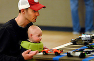 26 FEB. 2011 -- ST. LOUIS -- Matt Kelsey and his 4-month-old son Ben take a close up look at the pinewood derby cars during a pause in racing at the Adult Pinewood Derby sponsored by the Men's Club at Our Lady of Sorrows Catholic Church in St. Louis. Proceeds from the event, held at the church's parish hall Saturday, Feb. 26, 2011, benefitted the Boy Scouts of America. Image copyright © 2011 Sid Hastings.
