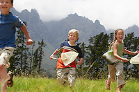 Three children (7-9) running through field with butterfly nets.