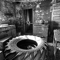 Abandoned home with derelict kitchen with large rubber tire in Rolette County USA