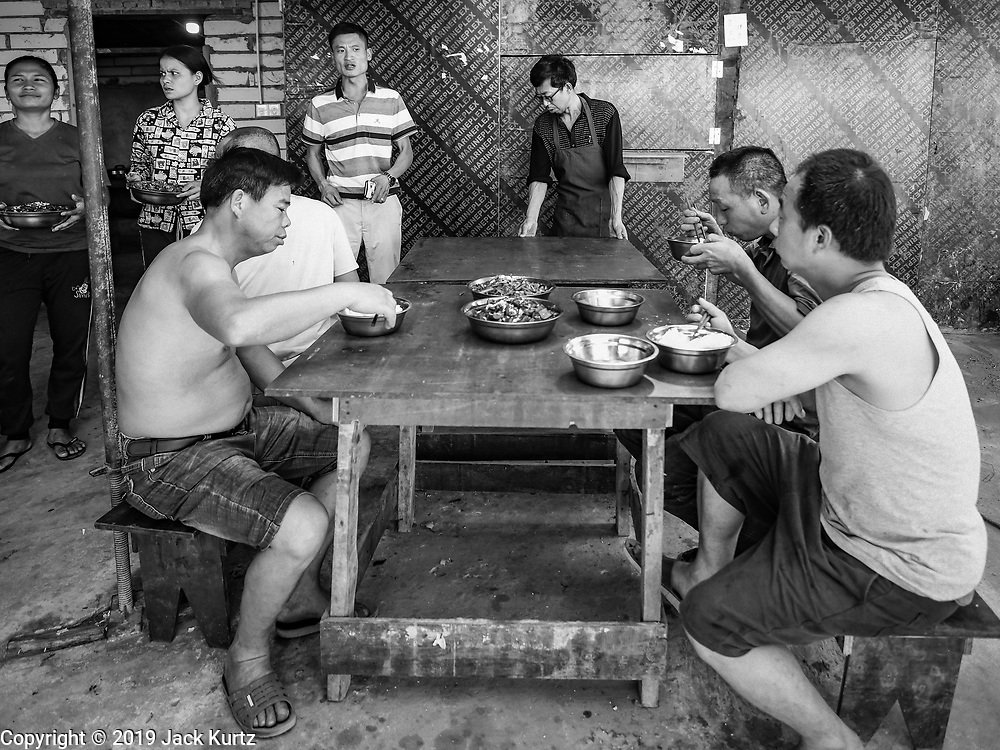 """15 FEBRUARY 2019 - SIHANOUKVILLE, CAMBODIA: A Chinese construction boss (background, striped shirt) talks to Chinese workers eating their lunch about the afternoon's work. There are about 80 Chinese casinos and resort hotels open in Sihanoukville and dozens more under construction. The casinos are changing the city, once a sleepy port on Southeast Asia's """"backpacker trail"""" into a booming city. The change is coming with a cost though. Many Cambodian residents of Sihanoukville  have lost their homes to make way for the casinos and the jobs are going to Chinese workers, brought in to build casinos and work in the casinos.     PHOTO BY JACK KURTZ"""